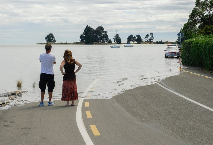 people looking at water over road, rising sea levels, climate change