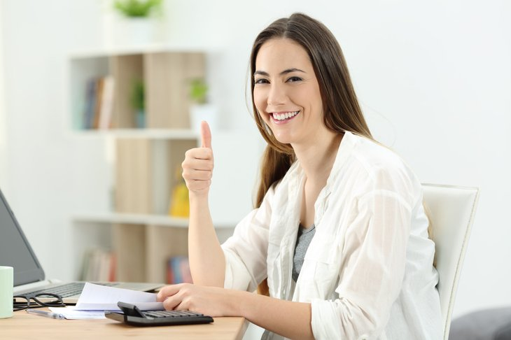 Smiling woman thumbs up taxes paperwork