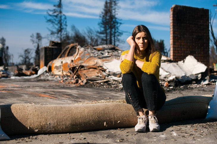 Woman sits outside her destroyed house