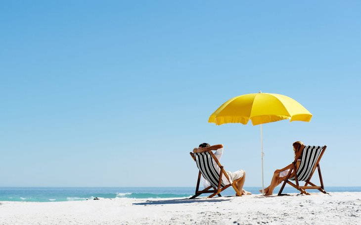Couple sitting on beach under umbrella