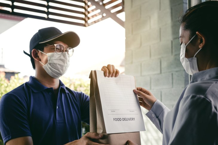 Making a food delivery while wearing a mask