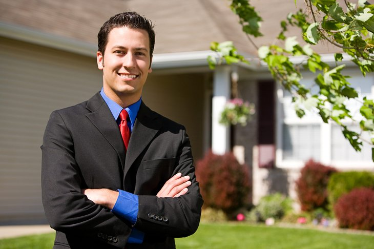 Real estate agent in front of a home for sale