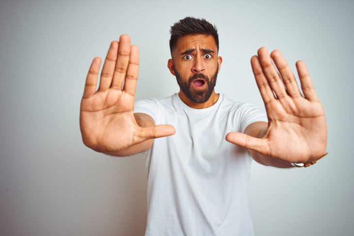 Worried man holds up hands in a stop or halt motion