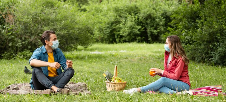 A picnic date between a couple with face masks during the COVID-19 pandemic
