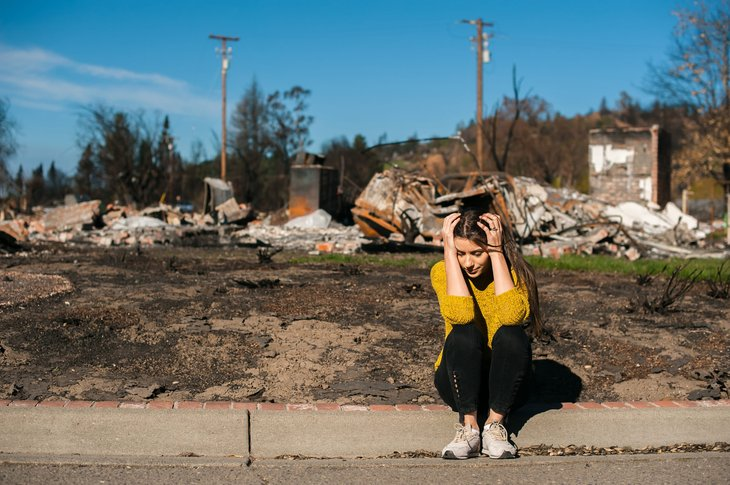 Woman outside her ruined home after a natural disaster or fire