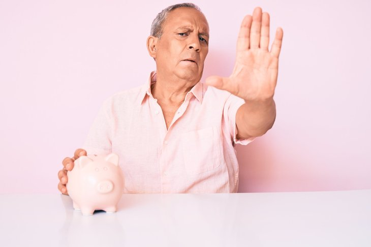 Senior man gesturing stop to protect his money