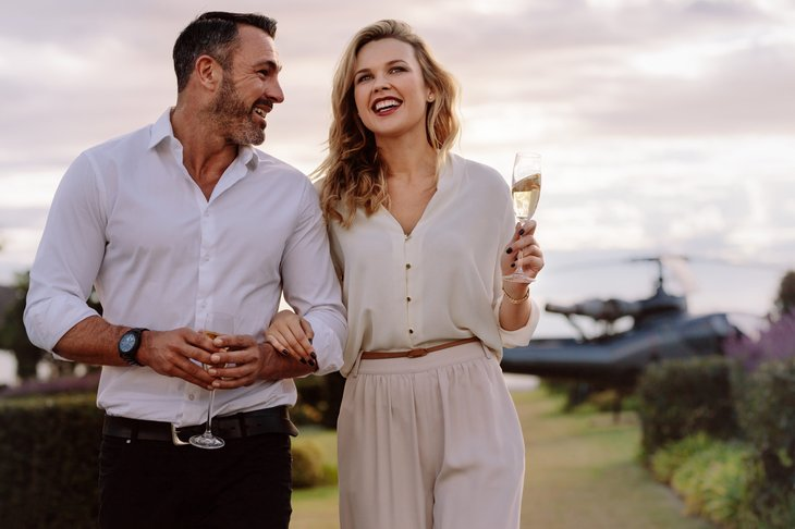 Affluent couple, sipping champagne, smiling and looking jolly