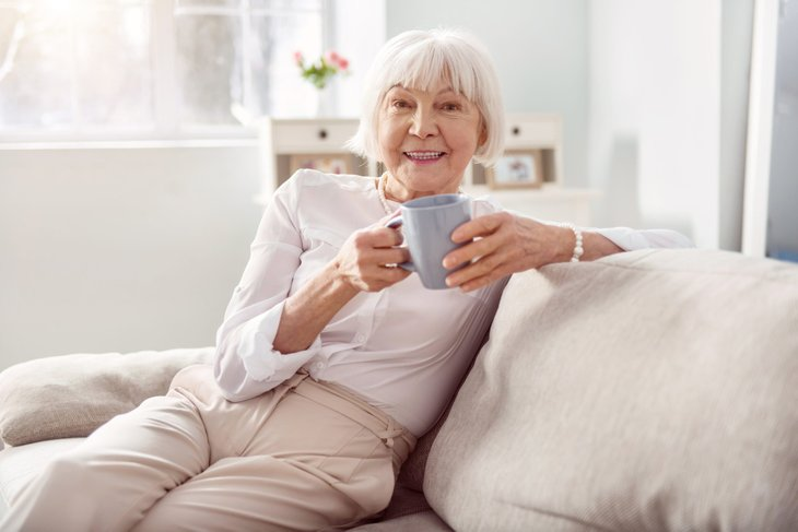 Senior drinking coffee at home