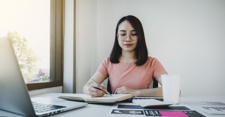 Woman writing down goals and organizing her financial plans