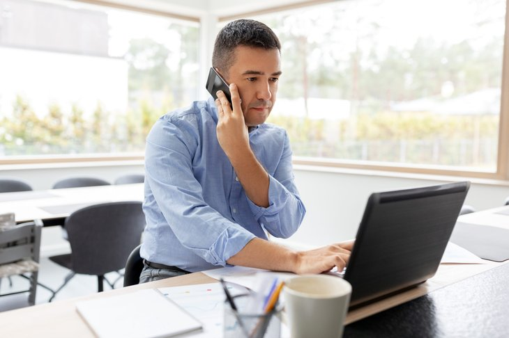 Remote worker on phone and laptop