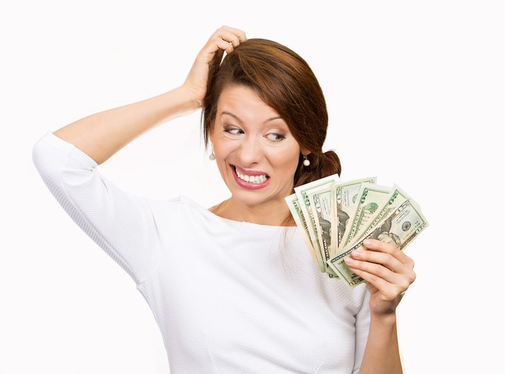 Confused woman holding cash