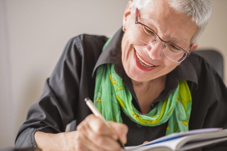 senior happy writing in notebook