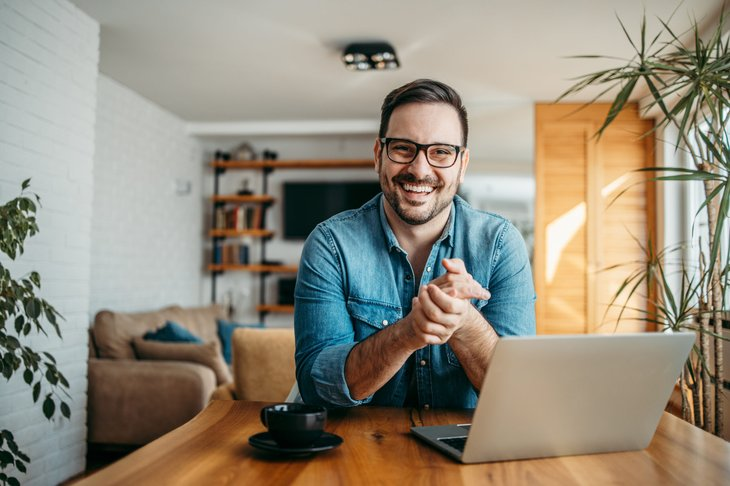 Happy man working in home office on laptop