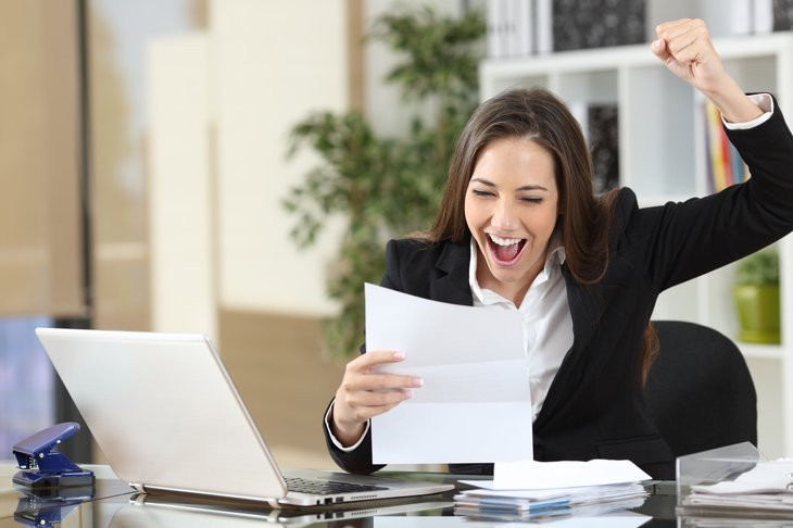 Excited businesswoman looking at a tax refund or other exciting business document