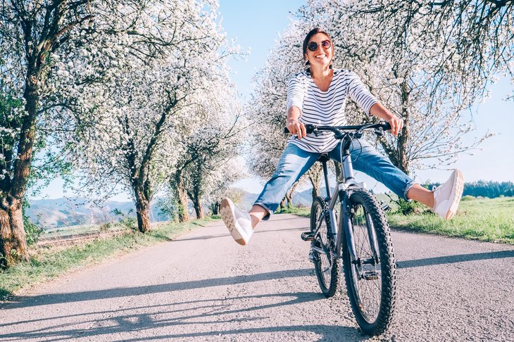 Happy woman riding bike outdoors in spring