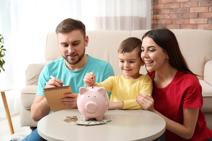 Parents and child saving money together