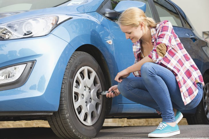 Woman checking air pressure on tires