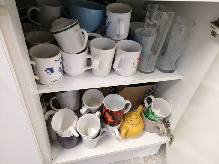 Mugs cluttering up a kitchen cabinet