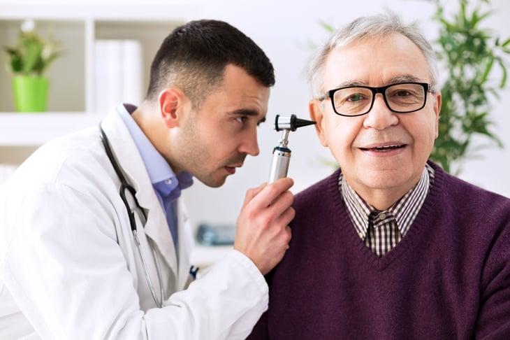 Doctor examining a senior patient's ear