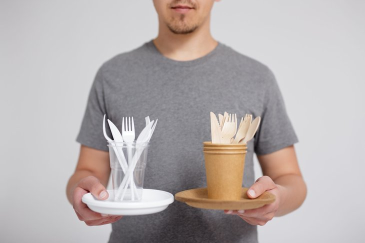 Man holding plastic and eco-friendly disposable cutlery