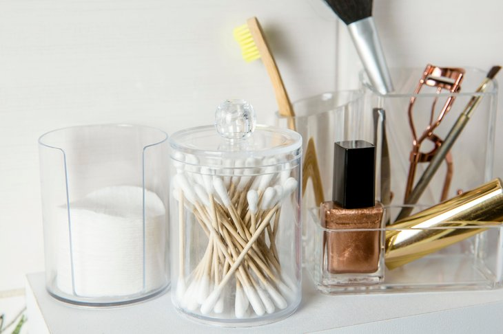 Cotton swabs and cotton pads next to makeup utensils