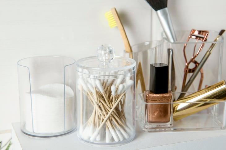 Bastoncillos de algodón y almohadillas de algodón junto a los utensilios de maquillaje