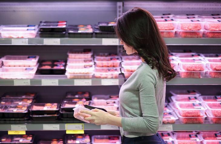 Mujer para compras de carne en una tienda de comestibles
