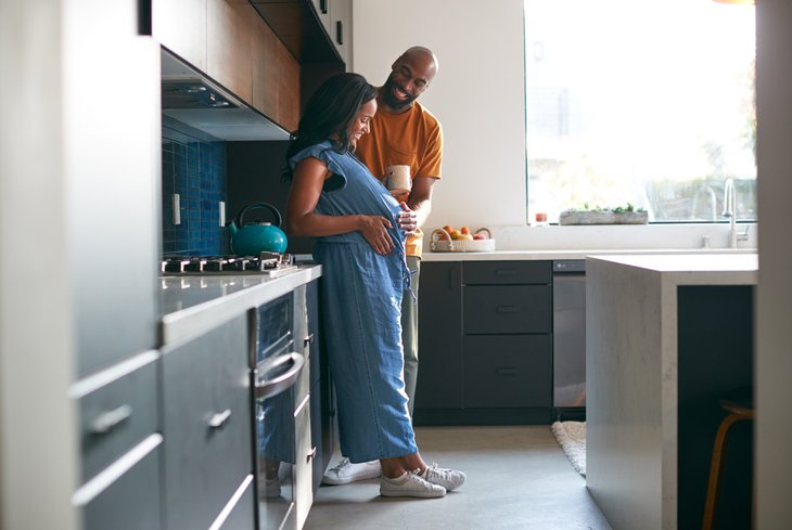 Happy pregnant couple in their kitchen