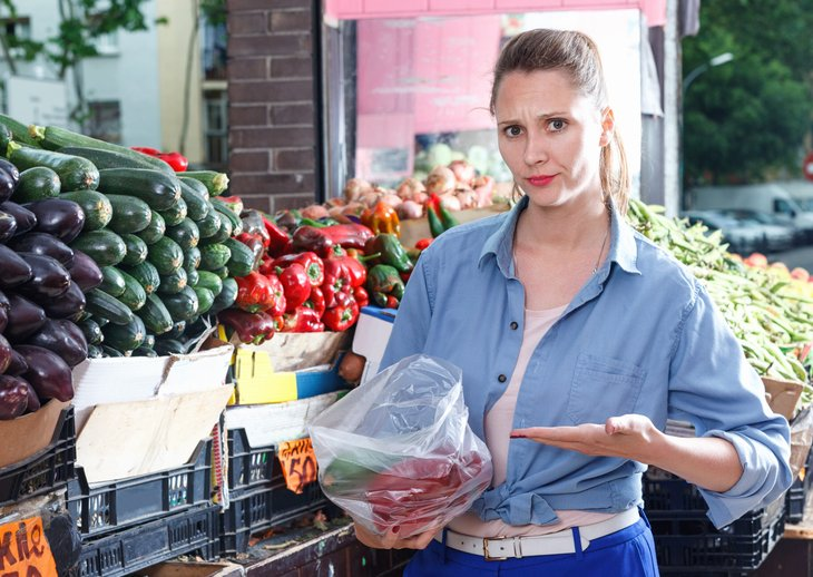 Unhappy woman grocery shopping