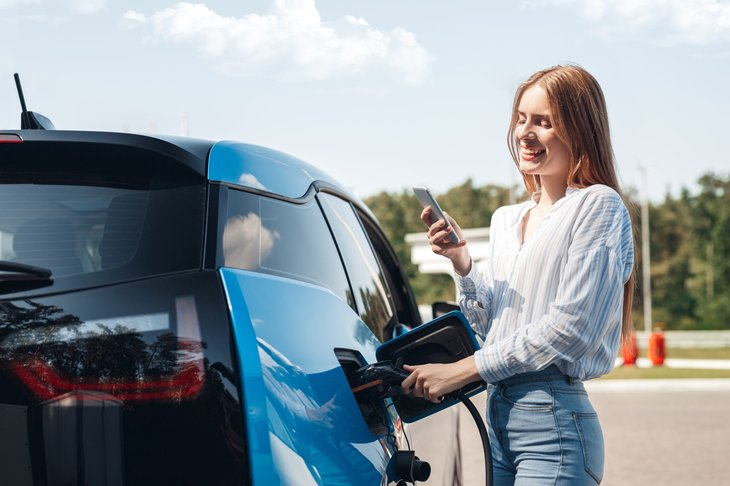 Woman charging her electric car vehicle