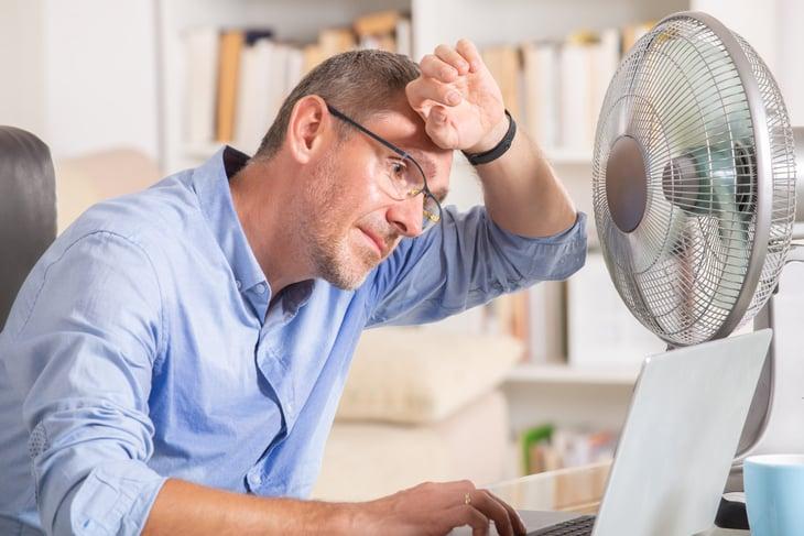 Man in front of fan on computer