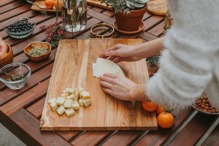 Preparing a charcuterie board with meats and cheeses and fruits