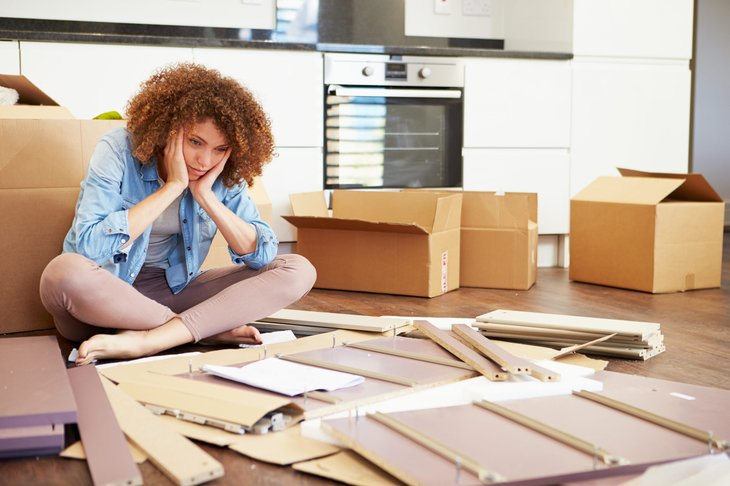Unhappy woman assembling furniture