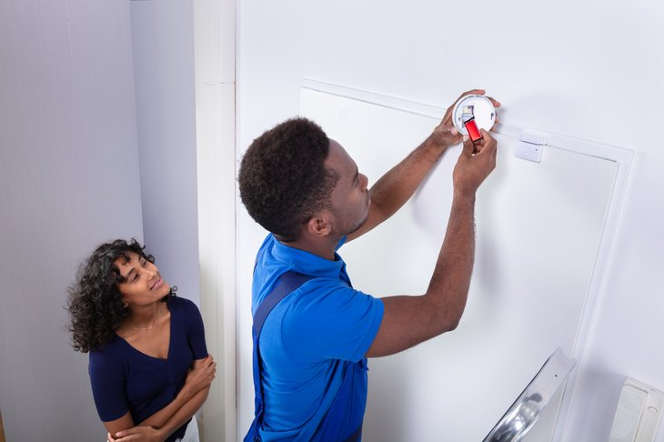 Man changing batteries in a smoke detector or alarm