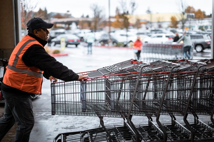 Costco worker pushing shopping carts