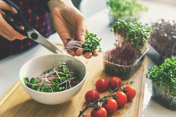 Woman making a salad with microgreens