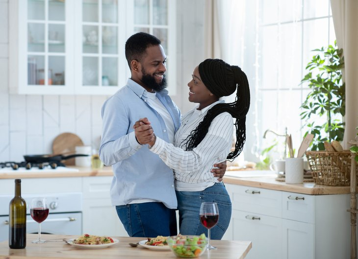 Happy couple dancing in their kitchen