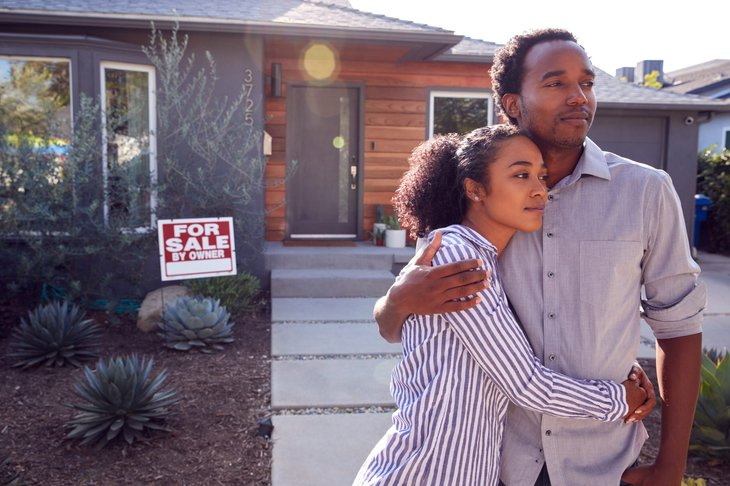 couple in front of home for sale by owner