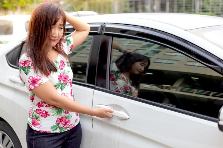 Unhappy woman standing next to a car