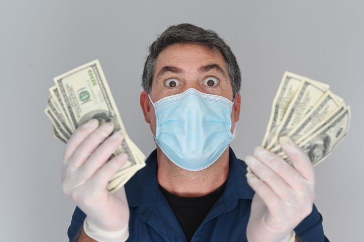 Excited man in face mask holding up lots of cash money