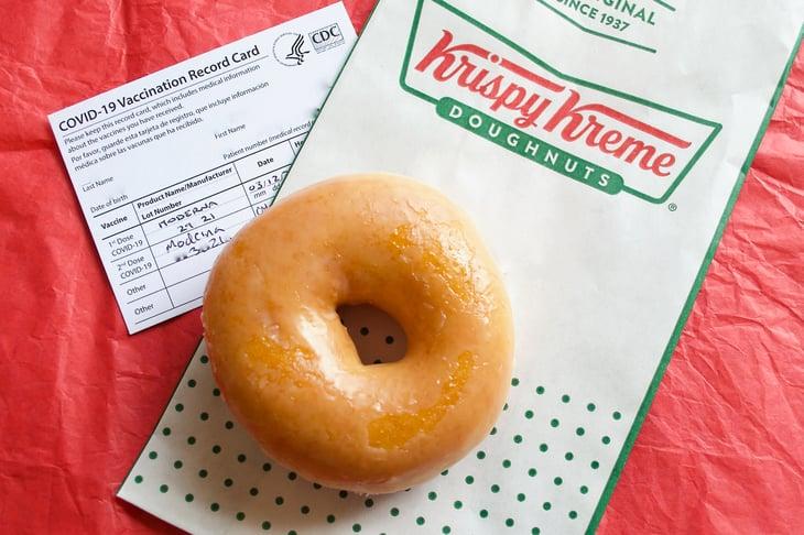A free Krispy Kreme Original Glazed Doughnut next to a COVID-19 vaccination card