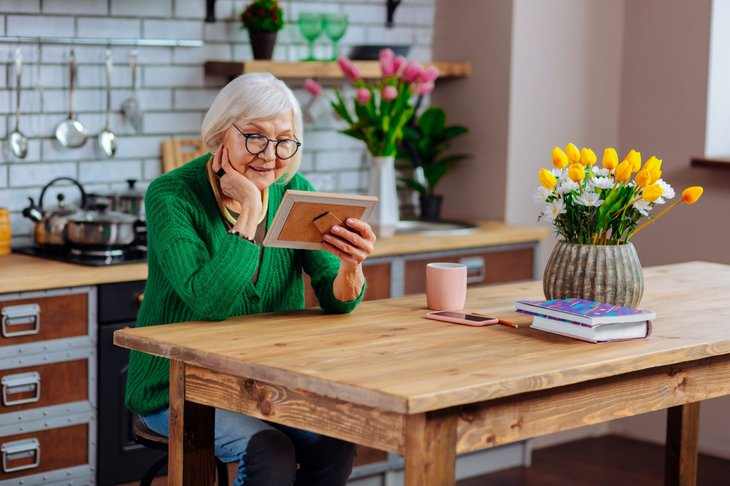Senior in glasses looking at a picture frame