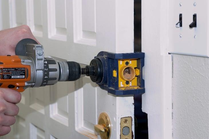 Worker installing a dead bolt lock