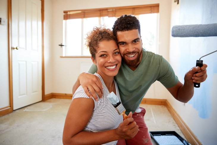 happy couple painting walls in home