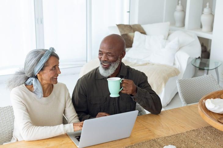 senior couple drinking coffee on computer