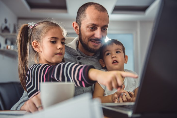Dad with two kids looking at computer