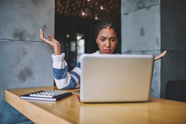 woman confused looking at laptop