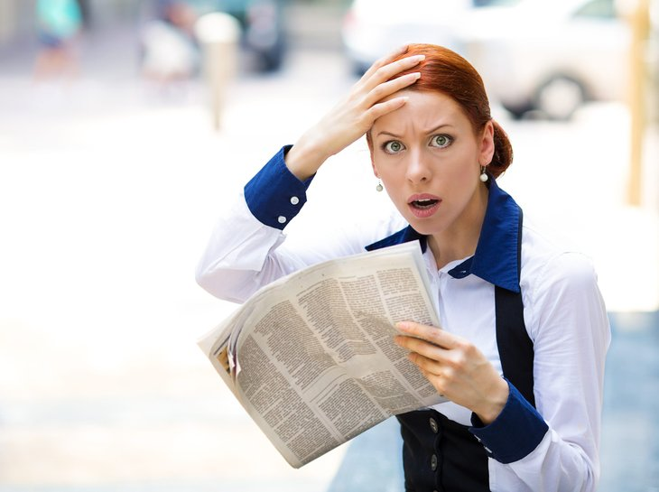 Shocked woman reading a newspaper.