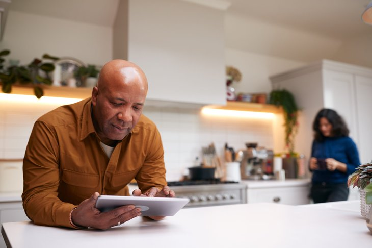 Man using a tablet computer in his kitchen while cooking