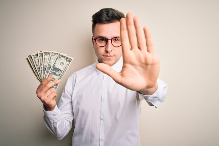 Man giving the stop gesture with one hand and holding cash with the other